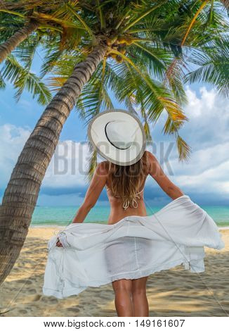 Woman at the tropical beach under the palm trees