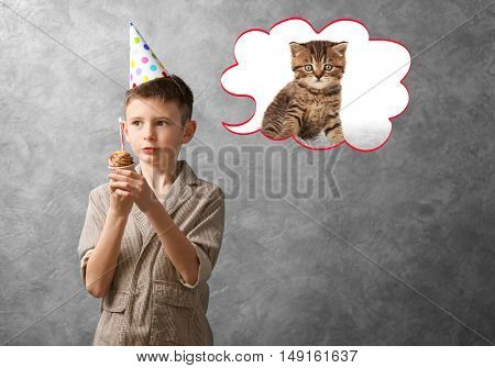 Little boy with cupcake dreaming about the cat on grey background