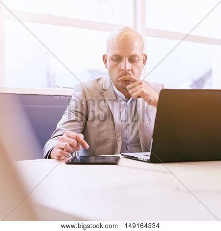 Business man working hard on his notebook and tablet early in the morning in the board room, concentrating and deep in thought while being productive.