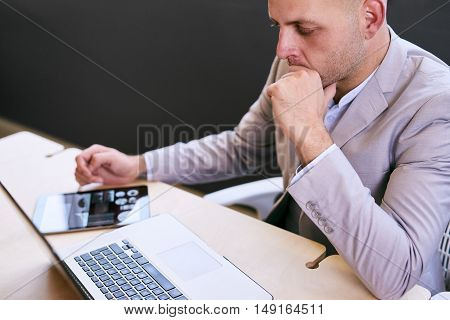 Business man working at table on his laptop and electronic tablet with graphics on the screen deep in thought while concentrating on his investment decisions.