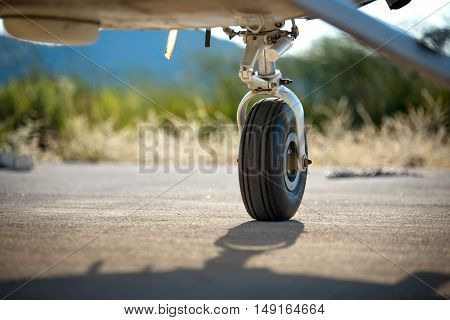 A rear landing gear and wheel chocks of a small aircraft on the ground with blurry nature and mountain in the background.