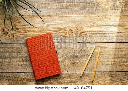 Comfortable working place at wooden table with notebook, pencil and flower