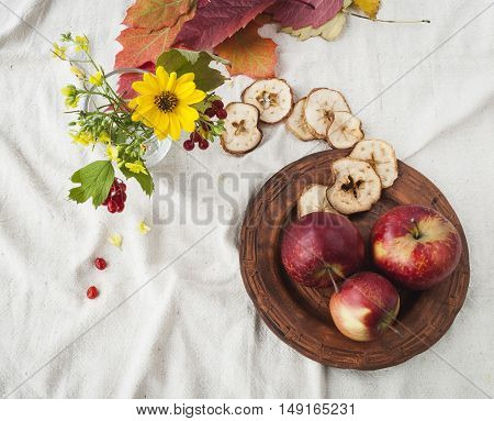 ripe apples in a beautiful plate, a bouquet of wildflowers, autumn leaf , red viburnum