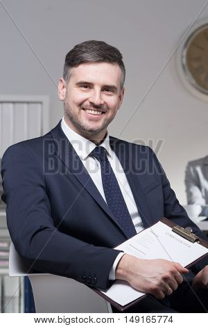 Youngsmiling handsome recruiter sitting on chair and holding applications
