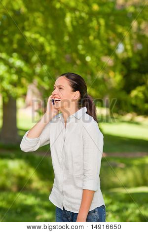 Young Woman Phoning In The Park