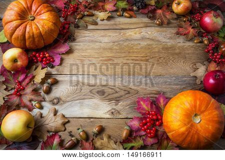 Frame of pumpkins apples acorns berries and fall leaves on wooden background. Thanksgiving background with seasonal vegetables and fruits.