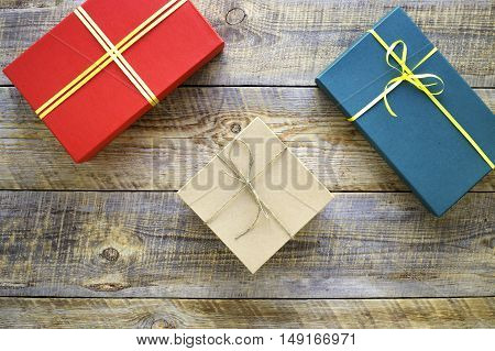 Colored gift boxes on wooden background with ribbon and straw - preperation.