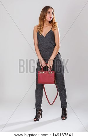 Full length shot of a fashionable young woman holding her handbag