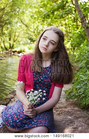 Beautiful Teenage Girl Sitting Beside A River
