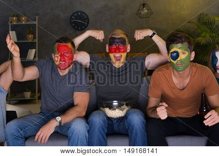 Shot of football fans with flags painted on their faces watching a game together