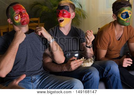 Shot of three football fans from different countries watching a game together