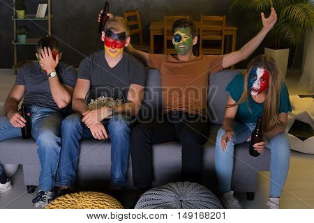 Shot of football fans from different countries watching a game together
