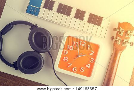 Music instruments object flat lay with orange clock face