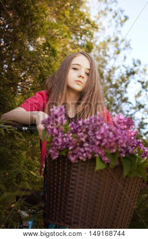 Beautiful Teenage Girl Sitting On A Bicycle With A Basket Of Flowers