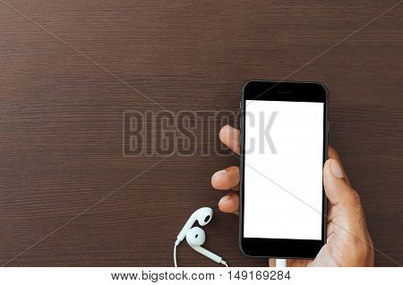 hand hold phone white screen on wood table mockup new smart phone modern style matte black color