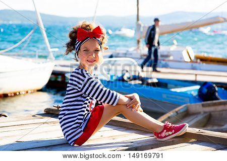 young girl sitting on the dock laughing and smiling looking around