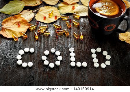 Concept of cold autumn - pills, leaves, tea on dark wood.