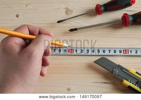 Hand with pencil measuring tape and other tools selective focus overhead view