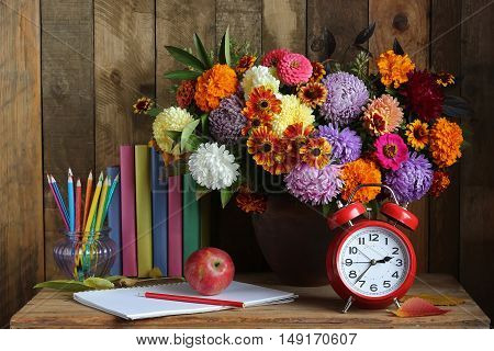Still life with a bouquet of fall flowers an alarm clock books and colored pencils. Back to school.
