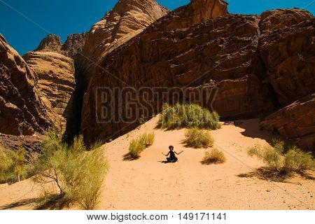 Photo of the Calm retreat concept. Girl relaxing meditation in Wadi Rum desert Jordan. Travel lifestyle summer vacations.