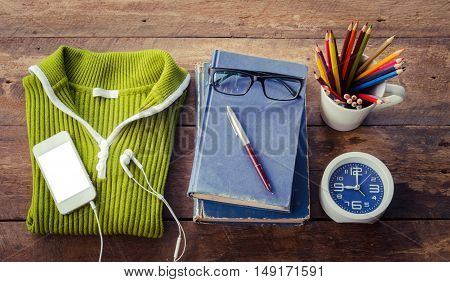 Accessories sweaters book pens glasses colored pencils clocks smart phones put on a wooden table