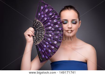 Beautiful woman with fan in fashion concept
