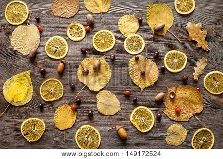 Autumn still life with orange caramel and cranberries on wooden background.