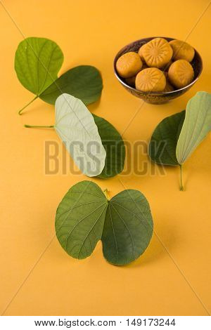 indian festival dussehra or vijayadashmi or ayudh puja, showing apta leaf or Bauhinia racemosa with traditional indian sweets pedha in silver bowl