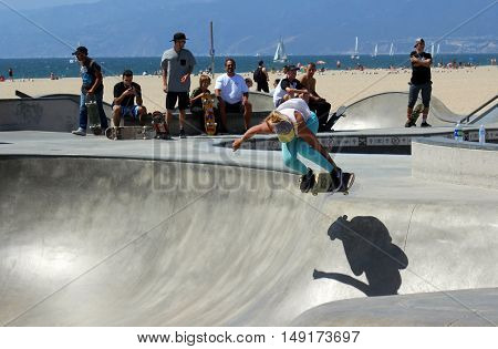 Los Angeles, California--9/5/16 Young teen girl on skateboard flies through the air above her shadow at Venice Beach Skate Park on Labor Day Weekend. Extreme skateboarding started here in Venice Beach.