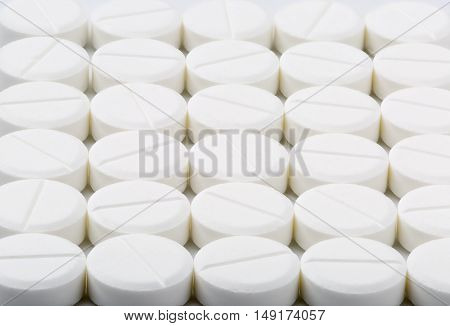 Round white medical tablets on bright background
