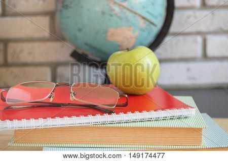 World teachers Day in school. Still life with books, globe, Apple glasses. selective focus
