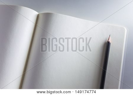 Opened blank white notebook and pencil on white background with side lighting