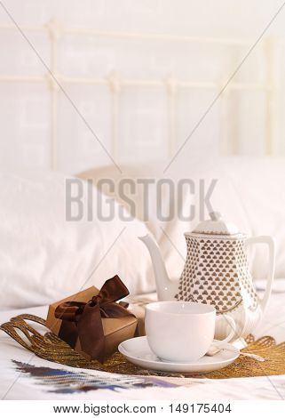Tea in bed with Christmas gifts - warm tone with plenty of copy space