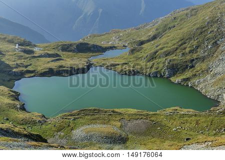 Mountain lake with crystal clear water of emerald color. Landscape from Capra Lake in Romania and Fagaras mountains in the summer.