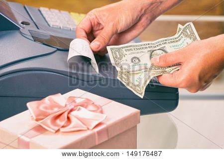 Seller using cash register and holding dollar banknotes at giftshop