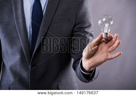 Businessman holding light bulb in creativity concept