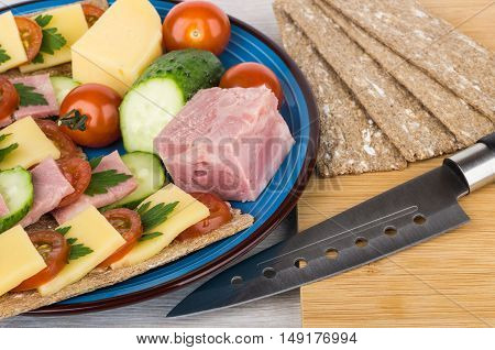 Plate Of Crisp Bread With Cheese, Bacon, Cucumbers And Tomatoes