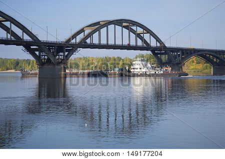 RYBINSK, RUSSIA - JULY 30, 2015: River tugboat with barges passes under the road bridge. Tourist landmark of the city Rybinsk