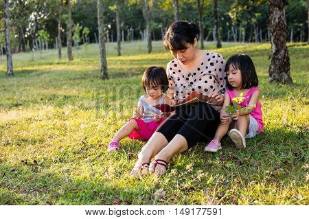 Asian Chinese Mother And Daughters Reading At Park