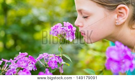 Young beautiful girl smells purple flowers in the garden - shallow depth of field