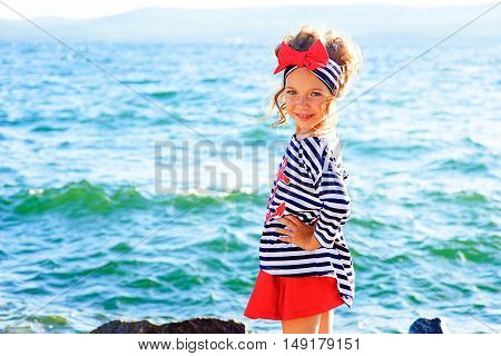young girl near the sea rock looking around and smiling