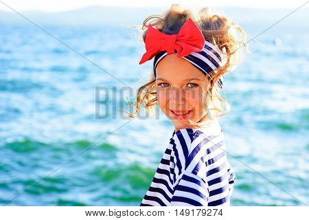 young girl near the sea looking around and smiling