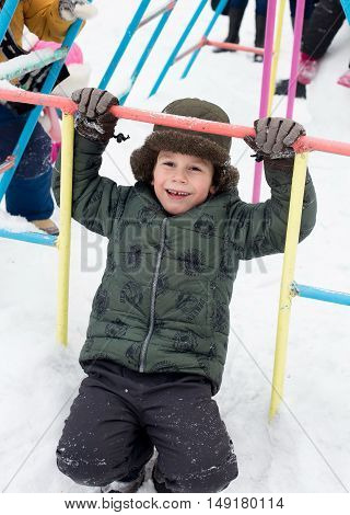 closeup portrait of Happy laughing children in winter clothes outside playing in the snow drifts in the winter