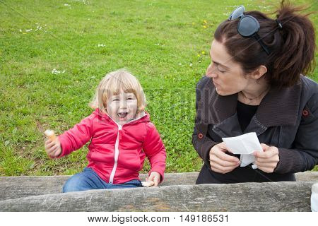 blonde cute child sitting eating bread piece and looking at camera next to woman in park with green grass background