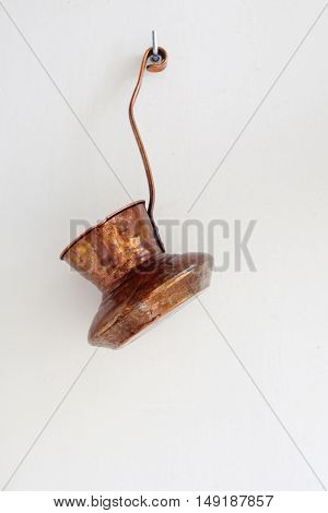 Copper coffee maker on the white wall background. Retro kitchenware hanging on a hook. vertical