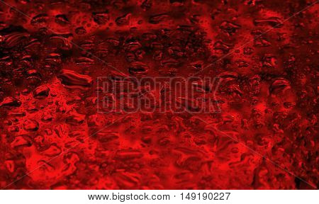 water drops on glass on a bright red background with patches of light rare black glare, blurred and abstract,