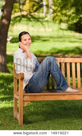 Young Beautiful Woman Phoning On The Bench