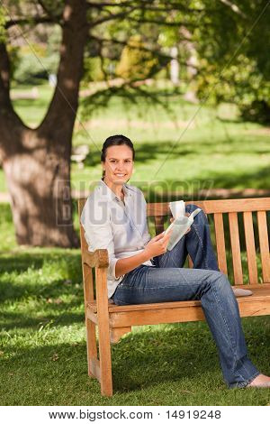 Young Woman Reading On The Bench