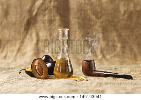 Plum brandy or schnapps with fresh and tasty plum fruit with tobacco pipe on a table cloth.