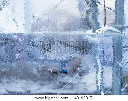 beautiful cold transparent wall of ice in the winter on the street